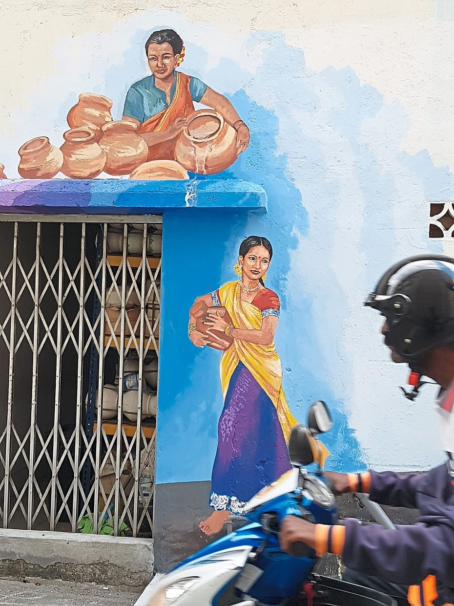 A mural of women carrying earthen pots colours the back wall of a shop that sells the wares.