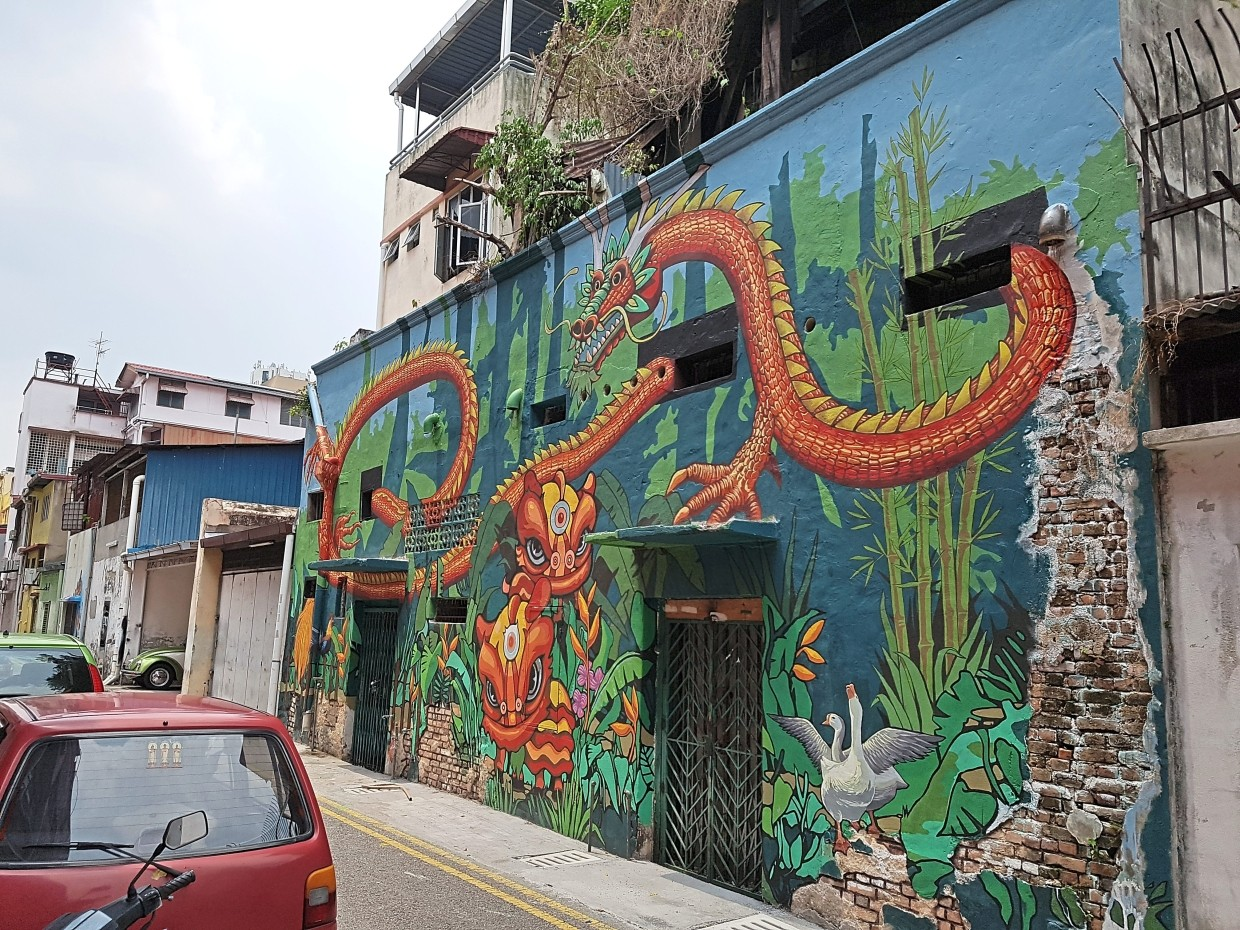 A vibrant mural of lions and dragons breathes new life onto the back wall of  a pre-war building.