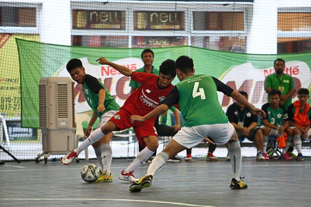 A player from Indonesian team Kamiada FC (in red) trying to dribble past his opponents during the finals