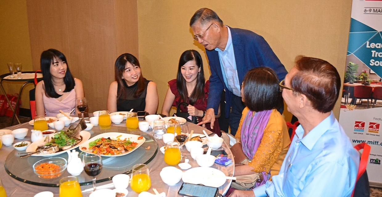 Dr Tan (standing) sharing an enlightening subject on furniture with exhibitors at the dinner.