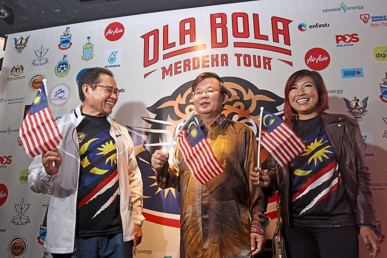 Chow (centre) and Tiara Jacquelina waving the Jalur Gemilang during the performance. With them is Jacquelina's husband, Tan Sri Mohd Effendi Norwawi.