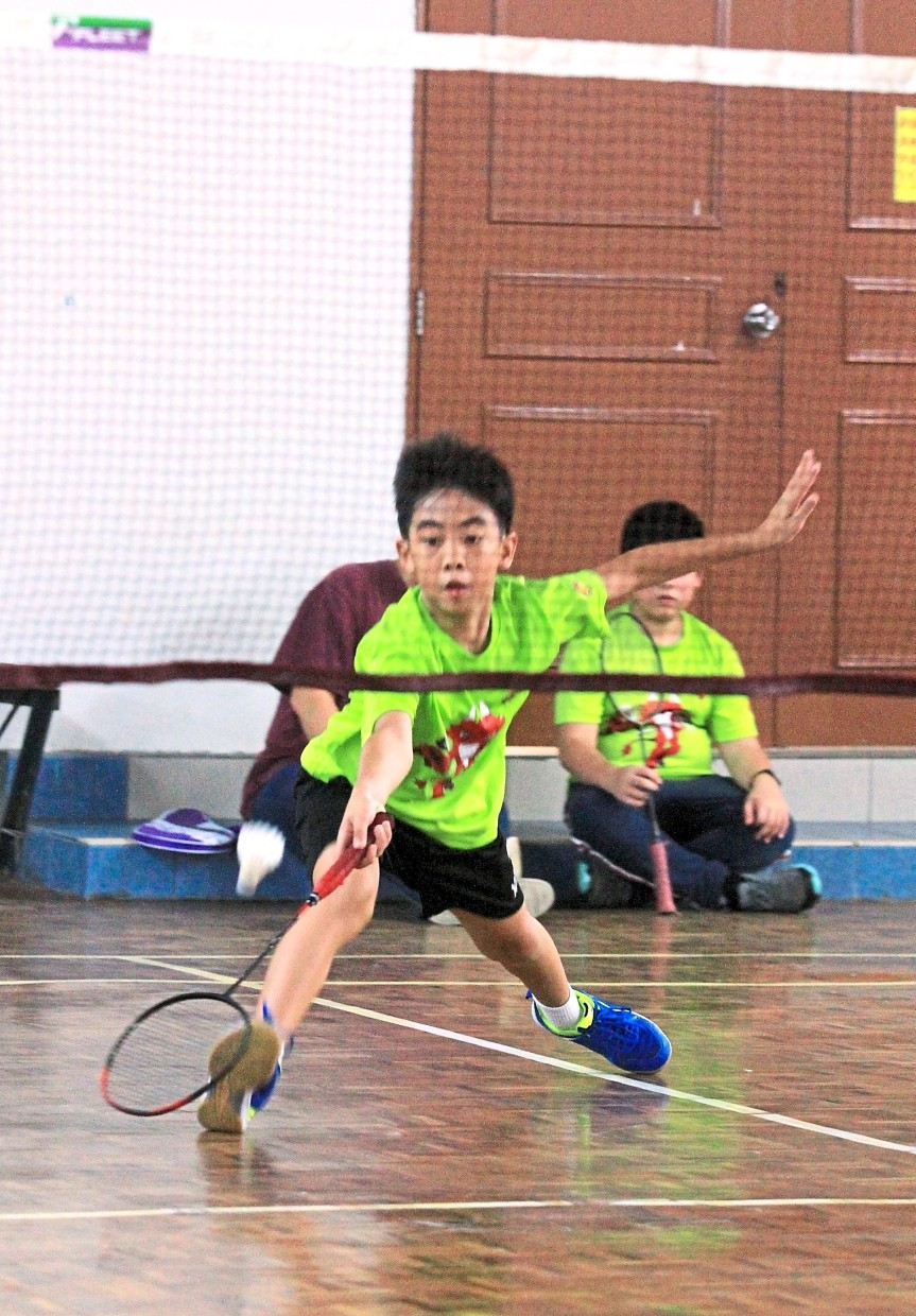A junior participant showing his badminton skills during the tournament.