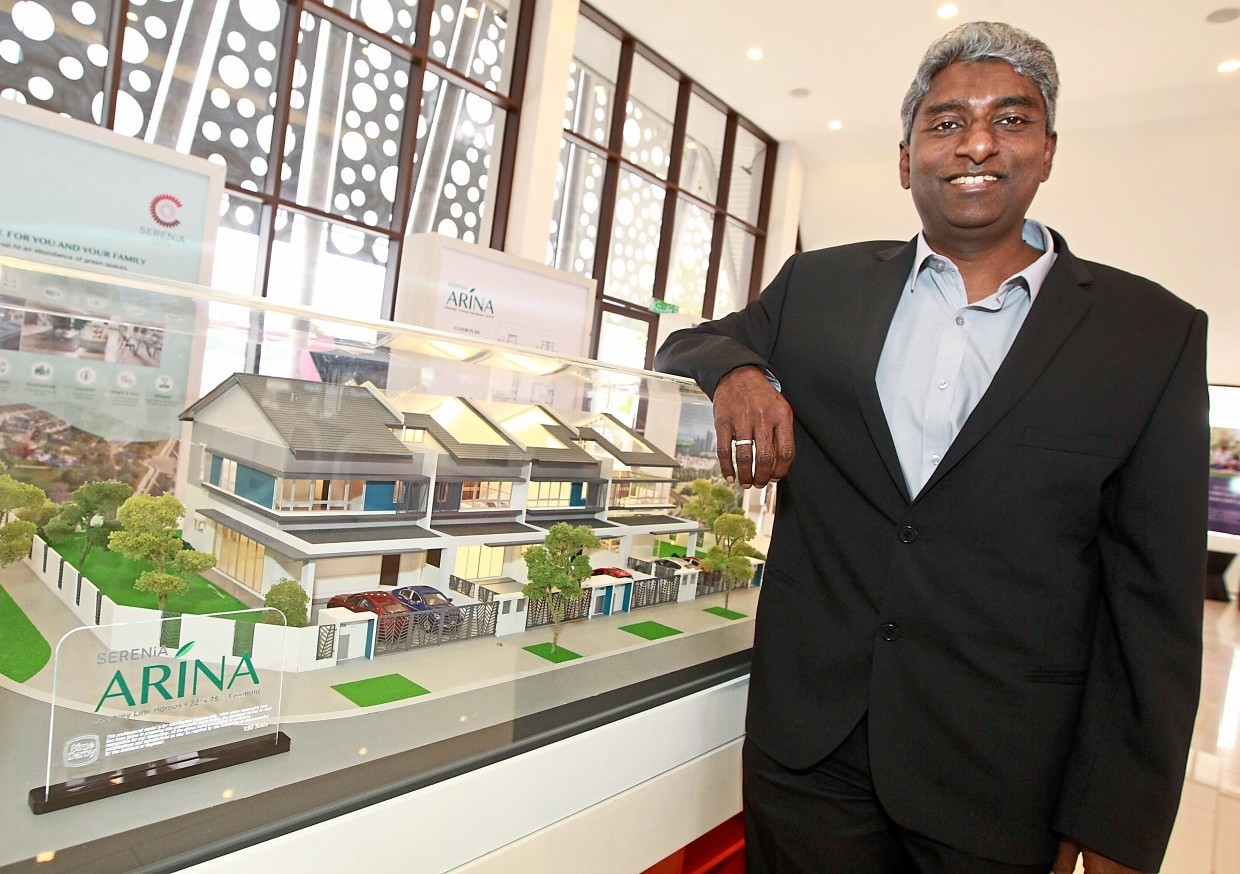 Positive sentiment: Idris posing beside a sales model at the Serenia City sales gallery in Sepang.