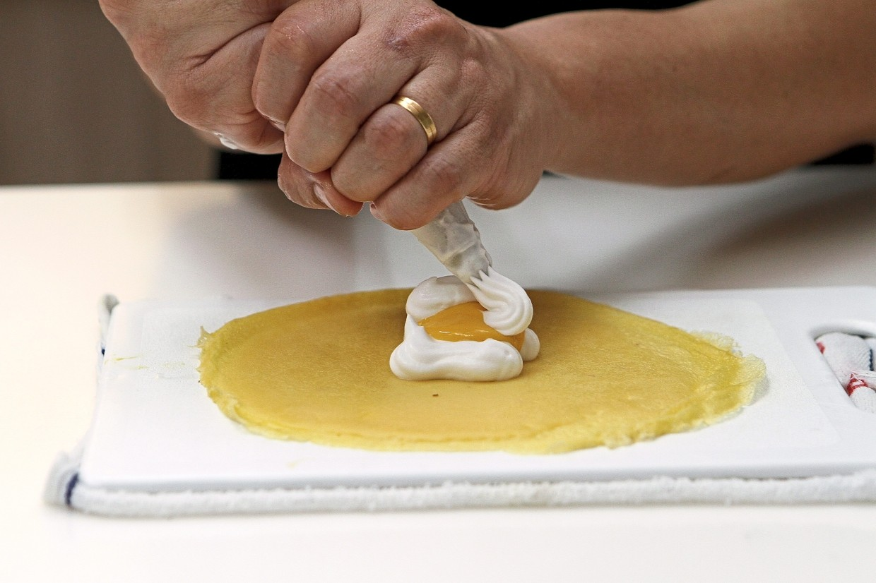 A layer of whipped cream is piped on the crepe, topped with a layer of durian custard, and then piped over with another layer of whipped cream.