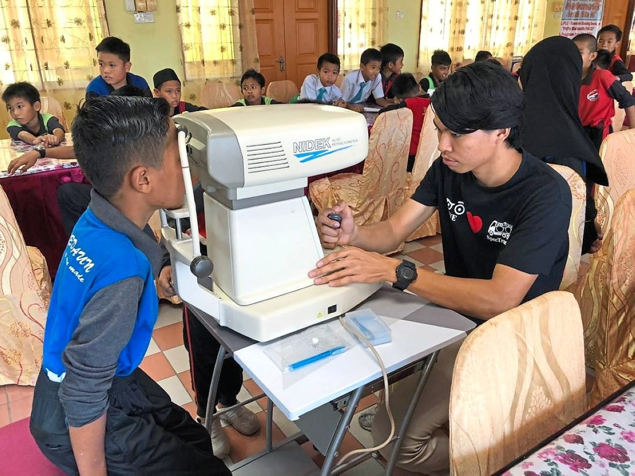 YWP's mobile unit conducting free eye checks at schools in Labuan, Sabah, and sponsored 3,000 spectacles for those in need.