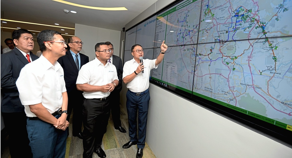 Amirudin (white shirt, centre) being briefed on the operations at the Air Selangor Intelligent Command Centre.