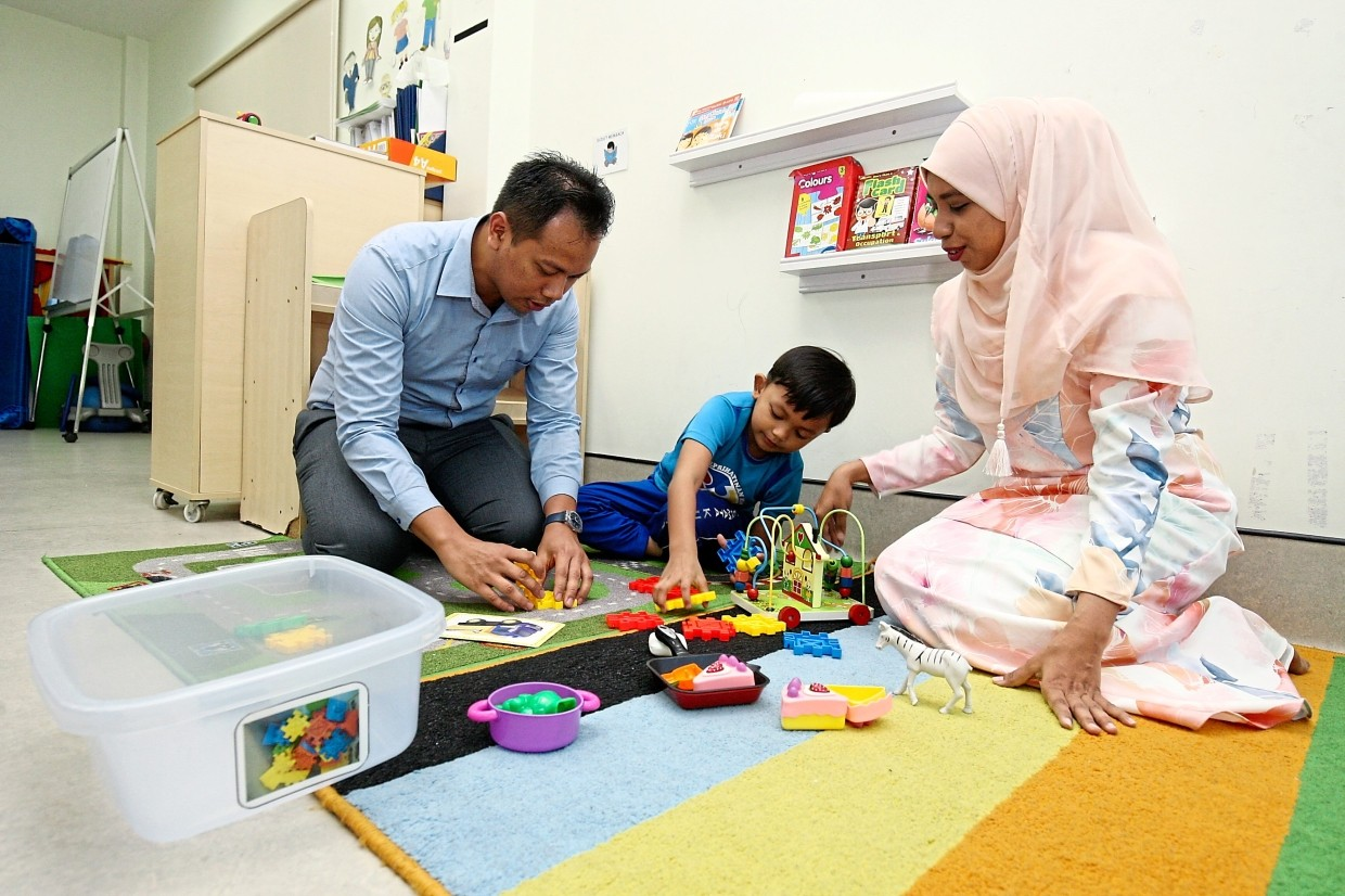 Muhammad Ammar, who has autism, playing with toys with his parents Dr Nur Farhana and Dr Mohammad at Genius Kurnia.
