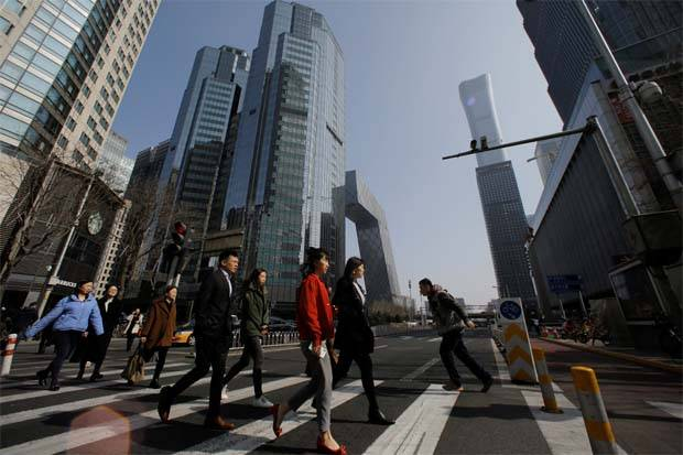 People cross a street in the Central Business District (CBD) in Beijing, China
