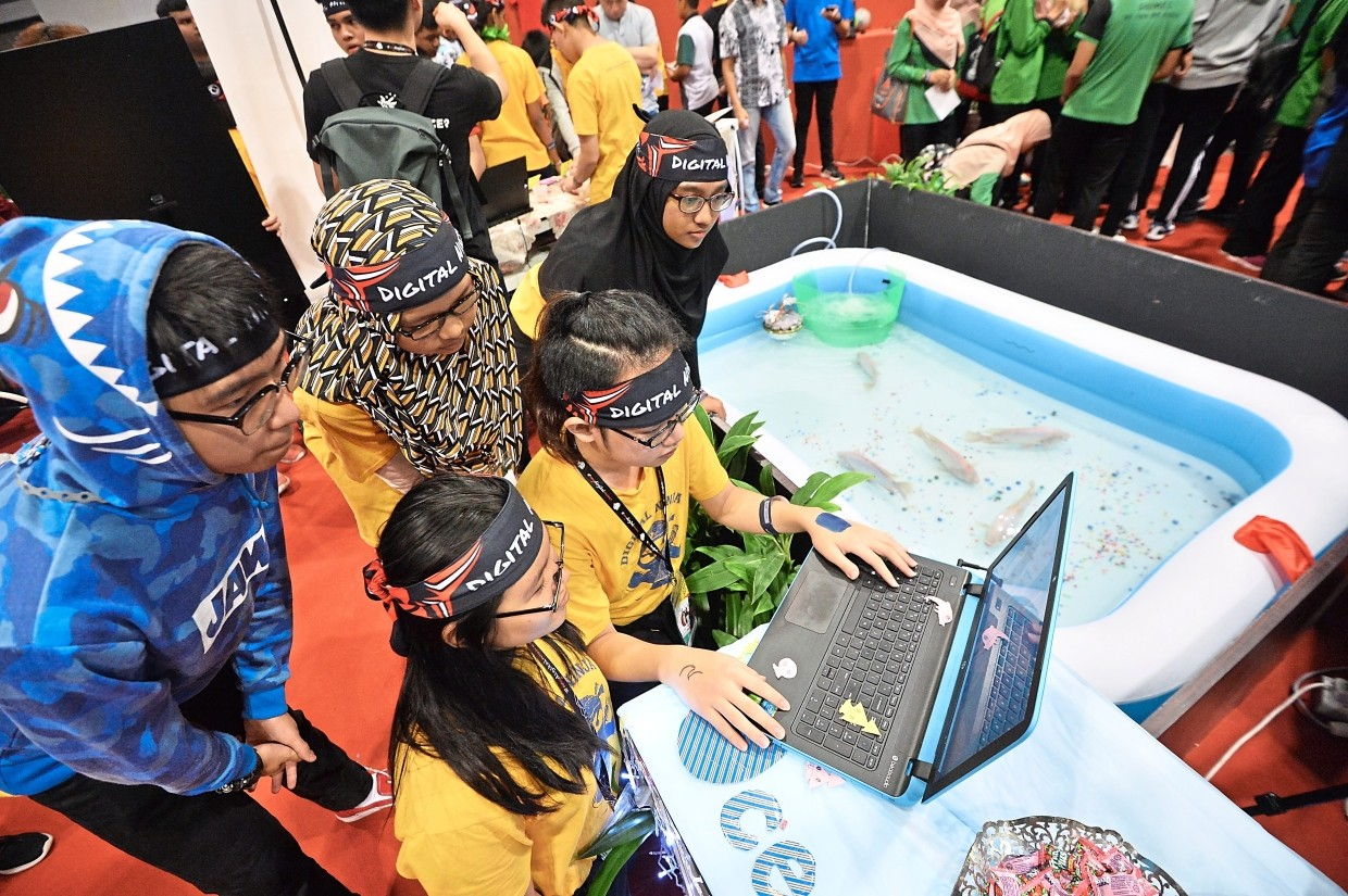 The Oceangold team comprising (standing, from left) Shaun Yoon Zer Khai, 15, Ainun Najwa, 13, Julia Hannah, 16, (seated, from left) Tracey Gwenevia, 16, and Jonathan Tan, 16, demonstrating how to operate Aufagold at their booth.