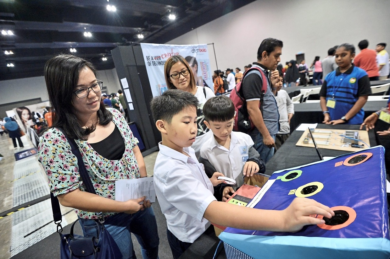 Mothers Ho (left) and Jacqueline Wong with their sons Jason (second from left), 10, and Wong Wen Tao, nine, who invented the 'Throw the Ball' game for the Junior Innovate 2019 competition by Chumbaka.