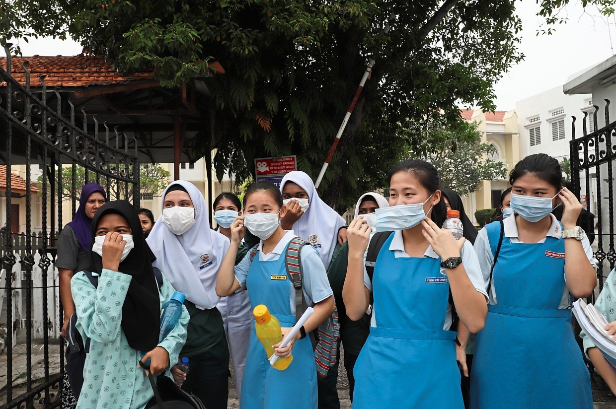 SMK Convent Light Street students putting on face masks as they wait for their parents.