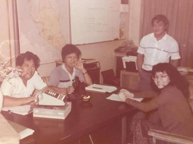 A young Raymond Tang (standing) with his staff at the first Agromate office, at Shaw Parade in downtown Kuala Lumpur.