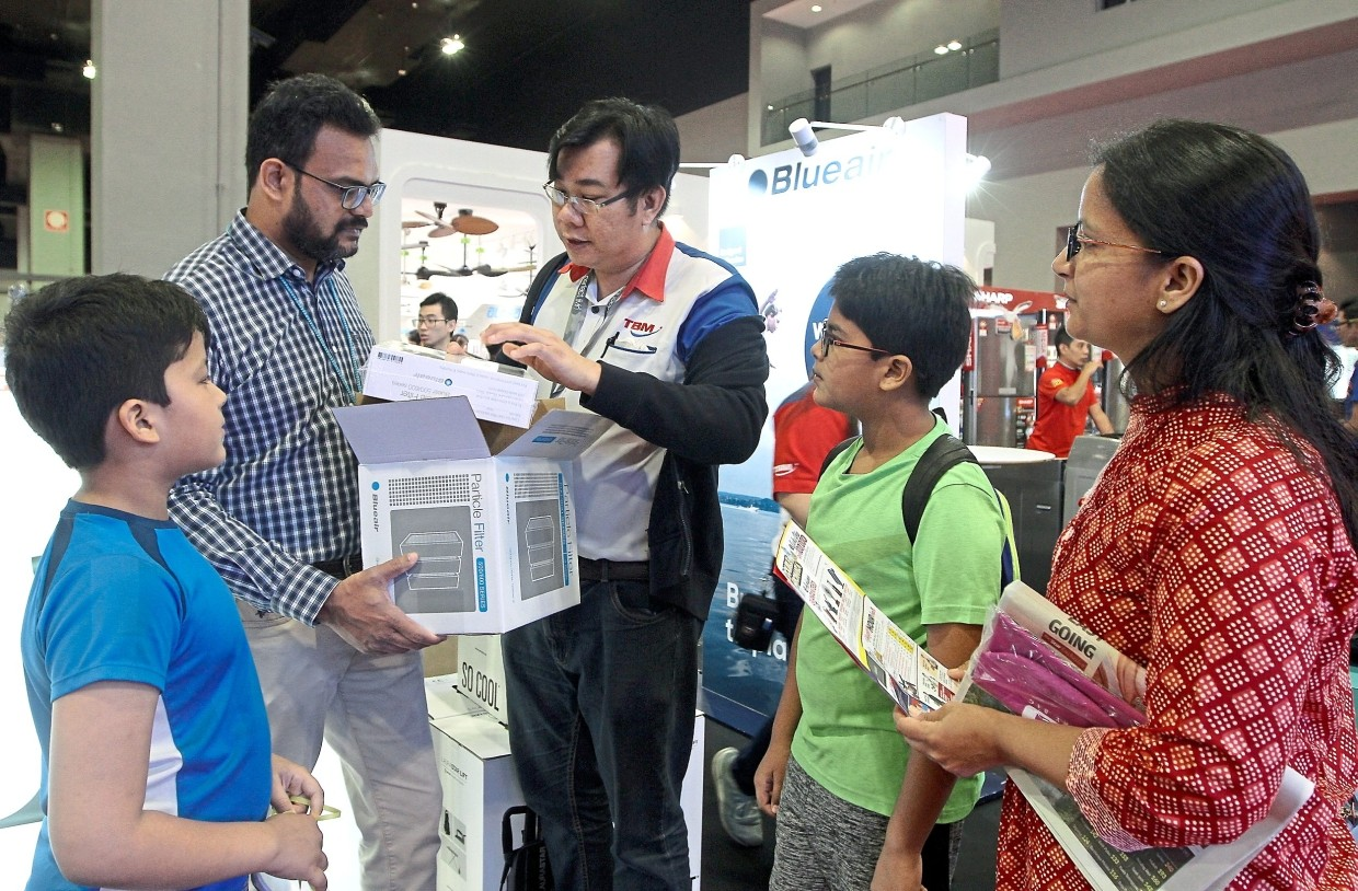 Rachana and her husband Praful Chakkarwar, 40, listen as a salesperson explains about the Blue Air air purifier while their sons Lohan (in green) and Namit (in blue) look on.