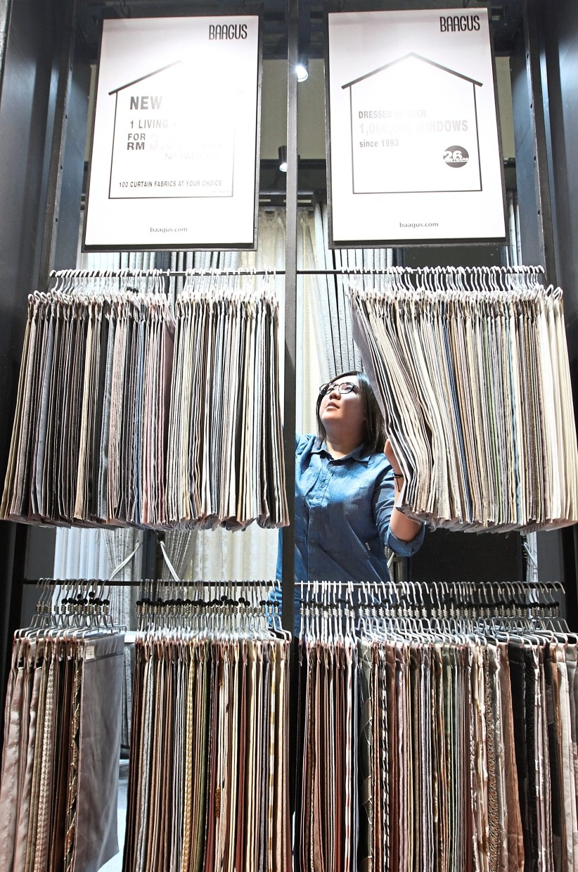 A Baagus salesperson arranging curtains at the booth.