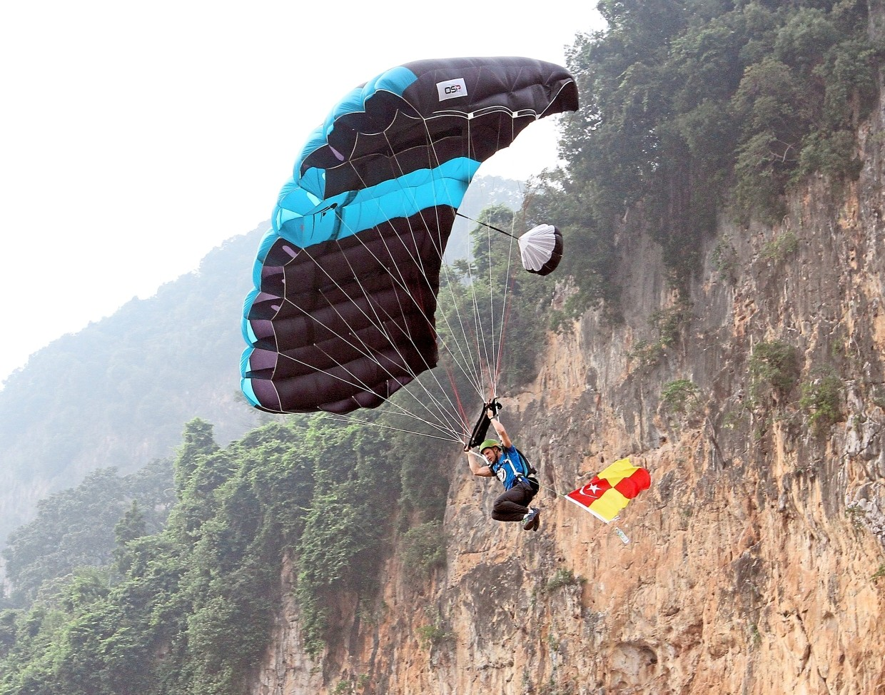 A participant making the jump with a Selangor flag as part of Malaysia Day celebrations.