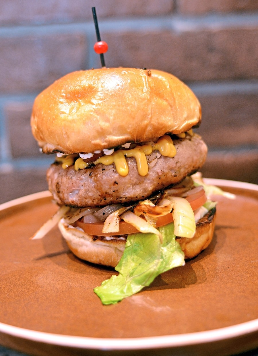 The homemade burger contains sauteed onion, iceberg lettuce, sliced tomatoes, grilled bacon and thick patty.