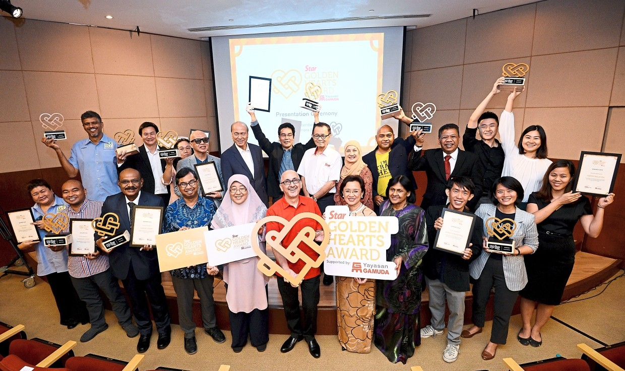 Worthy recipients: The top 10 winners of Star Golden Hearts Award together with chief judge Lee (back row, fifth from left) and fellow panel judges posing after the awards presentation ceremony at Menara Star. With them are Star Media Group Bhd chairman Fu (back row, middle) and chief executive officer Andreas Vogiatzakis (in red).