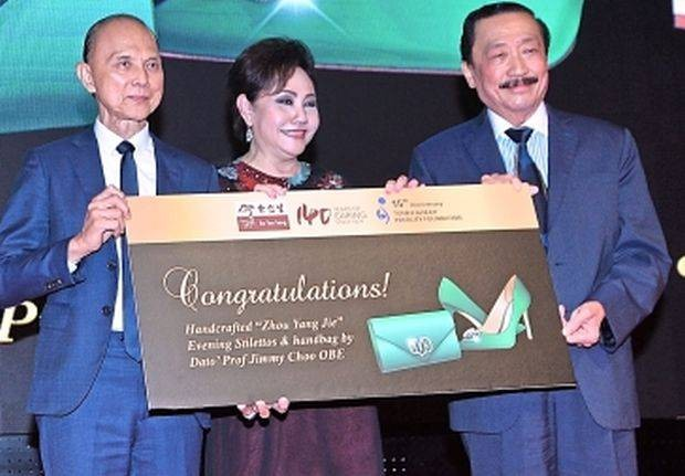Tan (right) won the bid for a pair of signature evening stilettos with a matching handbag designed by Choo (left). With them is Eu (centre).