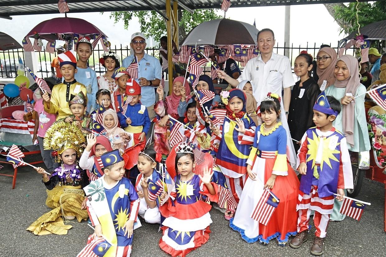 Muhammad Bakhtiar (blue shirt) and Ong (white shirt) posing with SK Padang Tembak pupils at the Malaysia Day celebration.