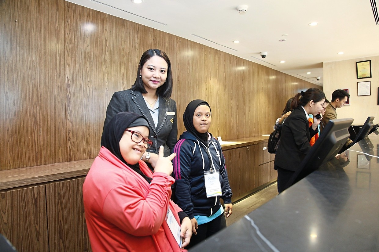 Two special youths getting hands-on experience at the hotel's front desk as part of their training.