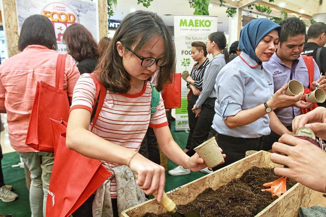 A shopper learning how to grow seeds by layering a container with compost and soil at the on-ground event.