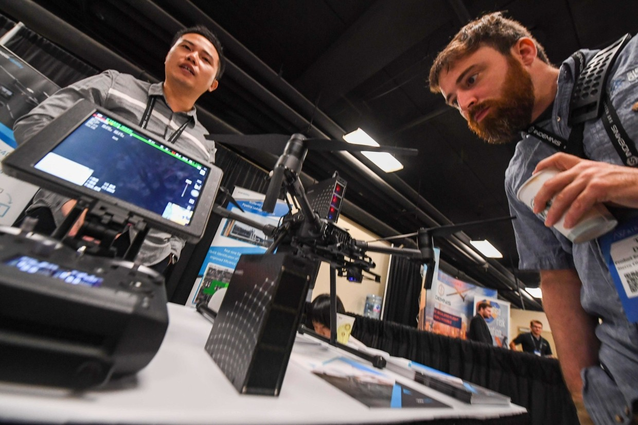 Attendees examining the Sniffer4D Air Pollution detection and mapping system from the Chinese firm Shenzhen Soarability Technology which is mounted aboard a DJI drone at DJI's AirWorks conference in Los Angeles, California.