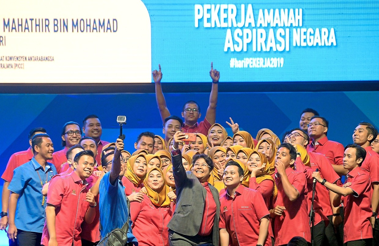 Higher income target: Workers taking a group photo during the Labour Day celebration in Putrajaya.  In pursuing a better standard of living for Malaysians, a key element will be to lift the wage to GDP levels of workers.