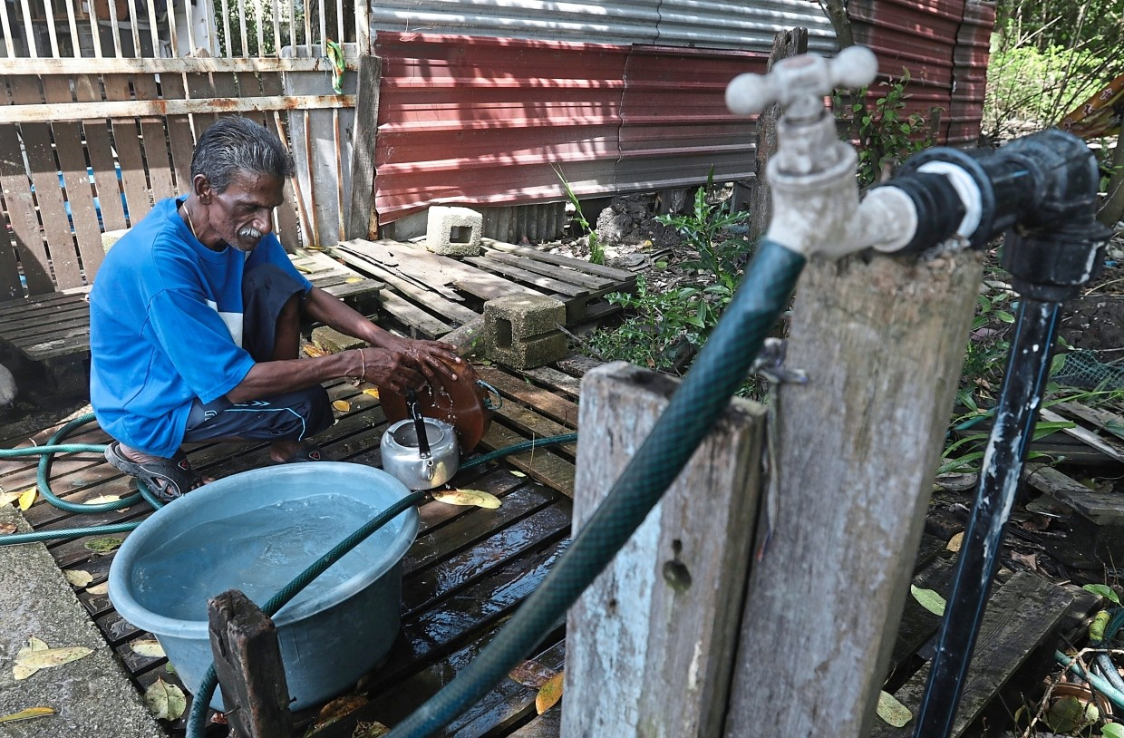 Grass cutter R. Gunasegaran, 50, has to fetch water from his neighbour's house in Kampung Manis, Penang. — ZHAFARAN NASIB/The Star