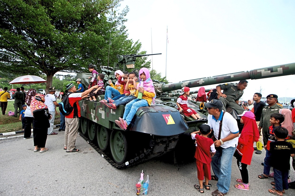 Children allowed to sit on a Armed Forces tank at the carnival. — Bernama
