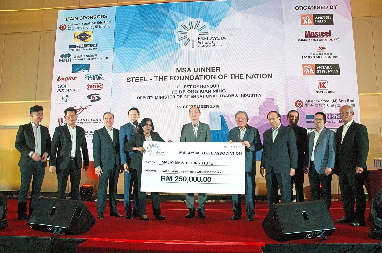 Mock cheque presentation: Cheng (fifth from right) presenting a mock cheque for RM250,000 to International Trade & Industry Ministry deputy secretary-general and MSI chairman Datuk Talagavathi Karapayah (fifth from left). The handing over was witnessed by Ong (centre). The money is for MSI to promote and develop the competitiveness, resilience and sustainability of the local iron and steel industry.
