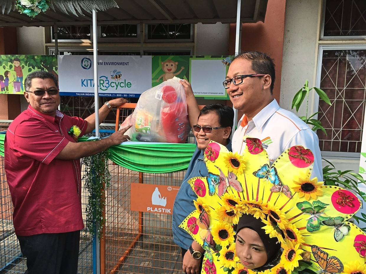 """Dzulkefly (left, red shirt) placing a plastic bag inside a recycling cage at the launch of SWM Environment Sdn Bhd's recycling programme dubbed """"Kitar3cycle"""" at SK Gelang Patah."""