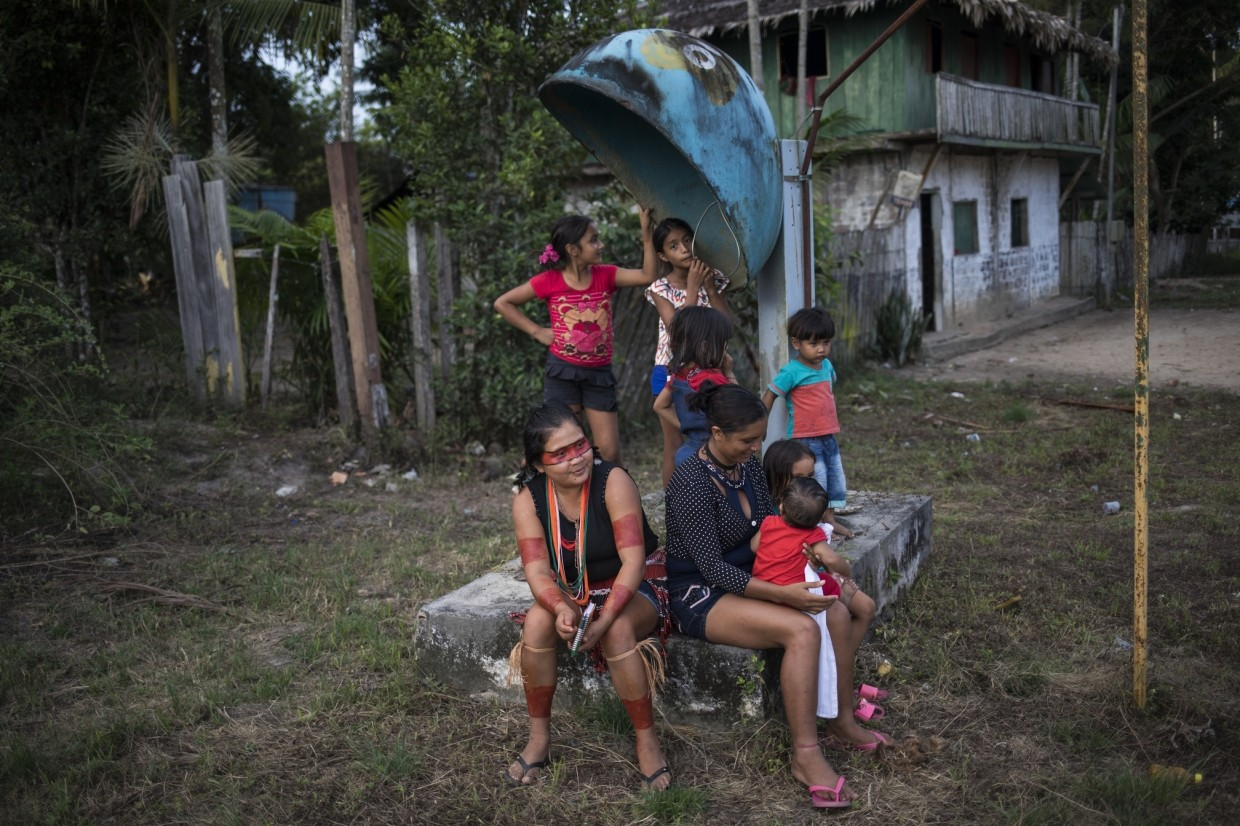Women and children congregate around an out of order public telephone after a gathering of Tembe tribe members in the Tekohaw village, in Para state, Brazil.