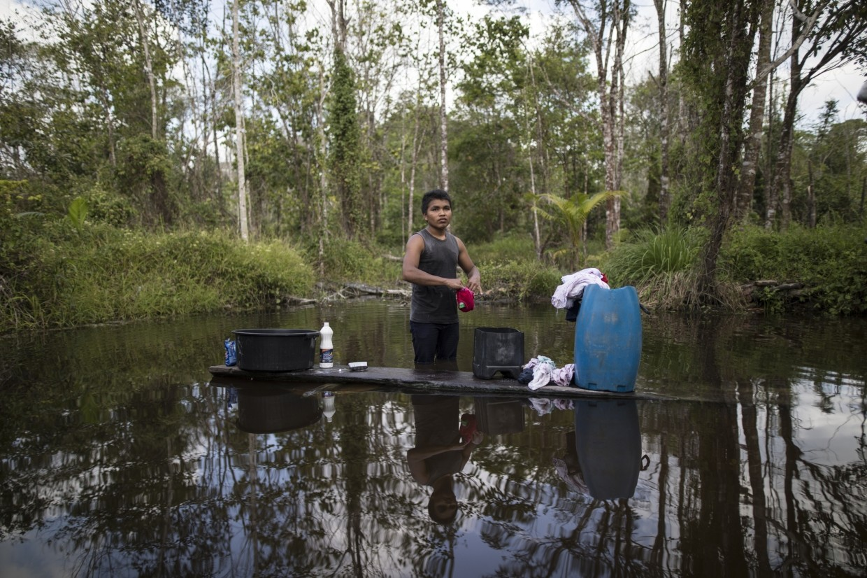 A young man washes his clothes in a pond in the viallge Ka 'a kyr, in Para state, Brazil. Villages along the Guama and Gurupi rivers that divide the Alto Rio Guama Indigenous Reserve can range in size from a few dozen people to hundreds.
