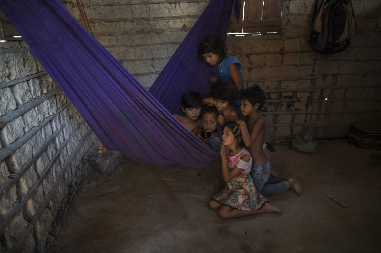Siblings and cousins gather around a cellphone on a purple hammock to watch a children's cartoon on YouTube, in the home of Gleison Tembe in the village Ka 'a kyr, Para state, Brazil.