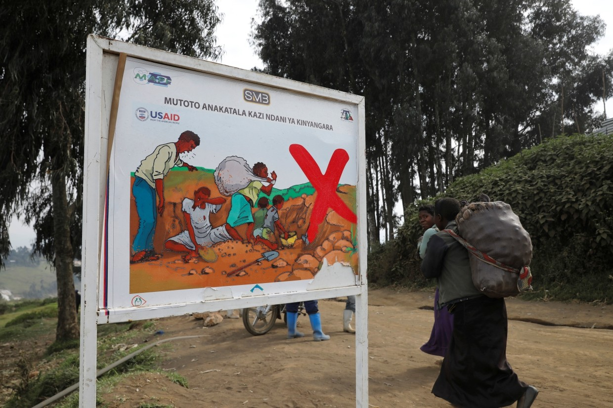 Women walking past a sign warning against a child labour at the SMB mine near the town of Rubaya in the Eastern Democratic Republic of Congo.
