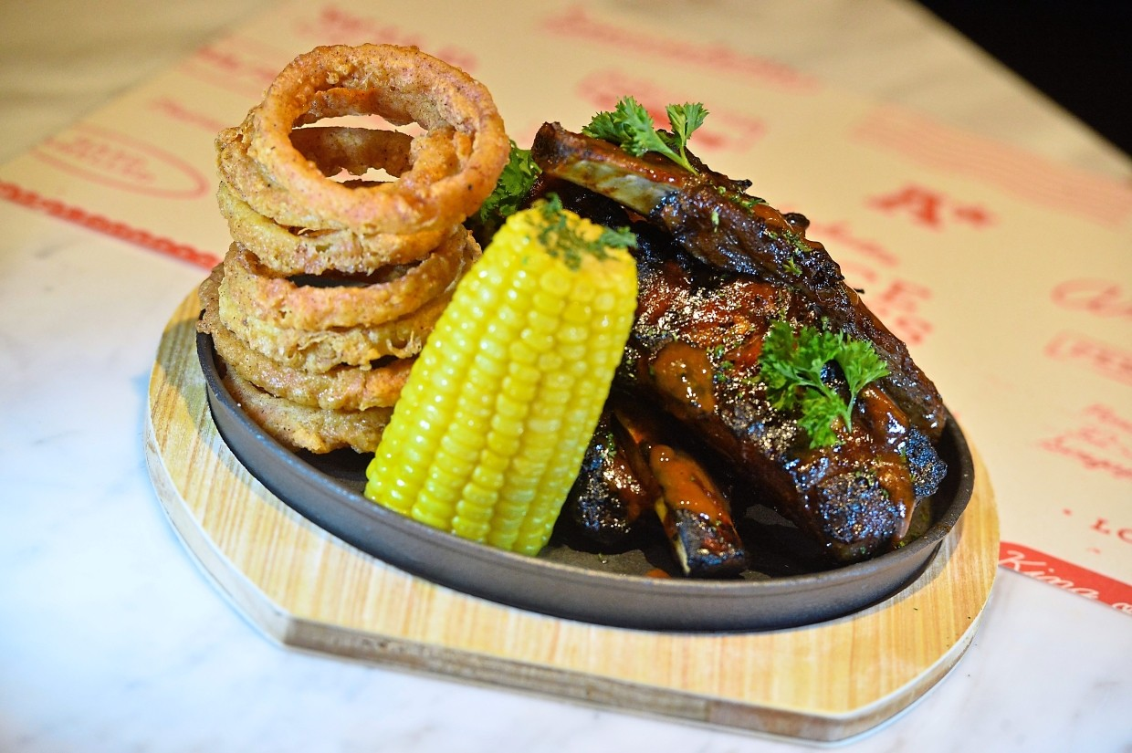 Beef ribs accompanied by corn on the cob and onion rings is a must-try.
