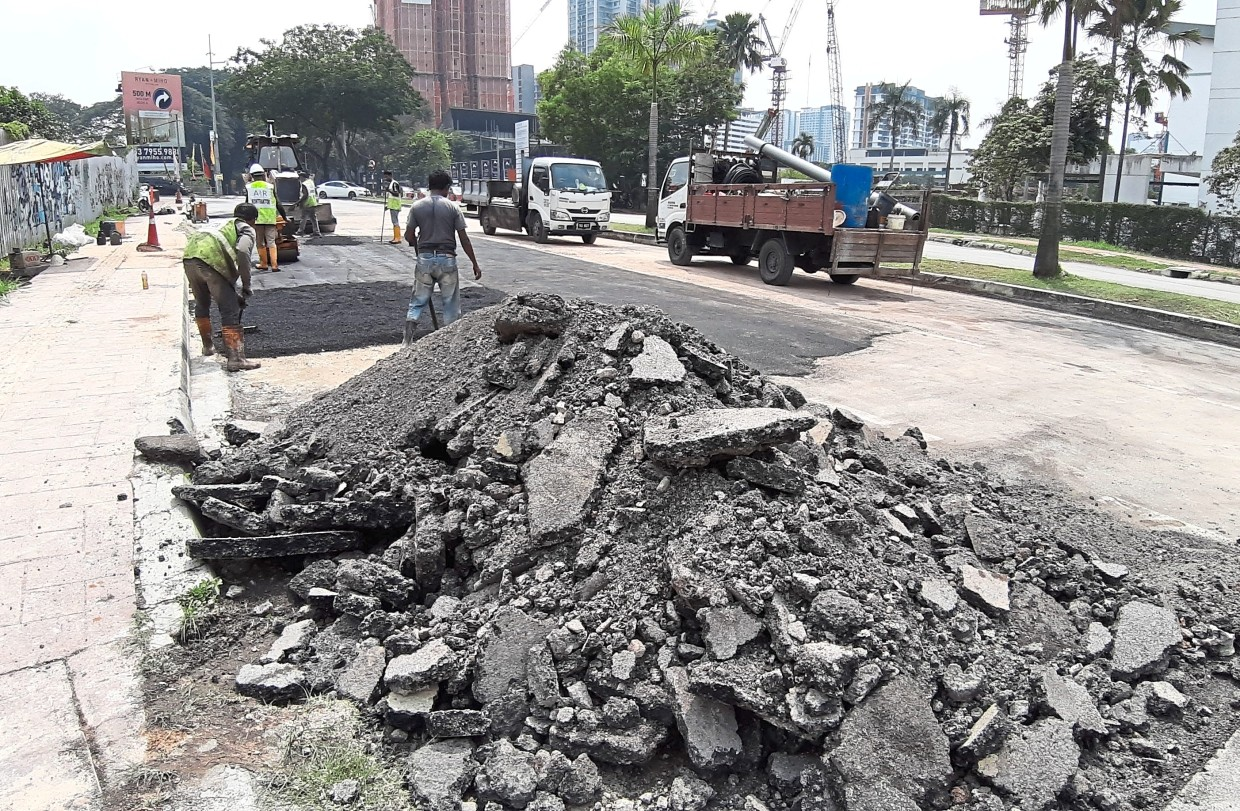 Air Selangor contractors resurfacing the affected area along Jalan Universiti in Petaling Jaya after completing repair works on the pipe yesterday.