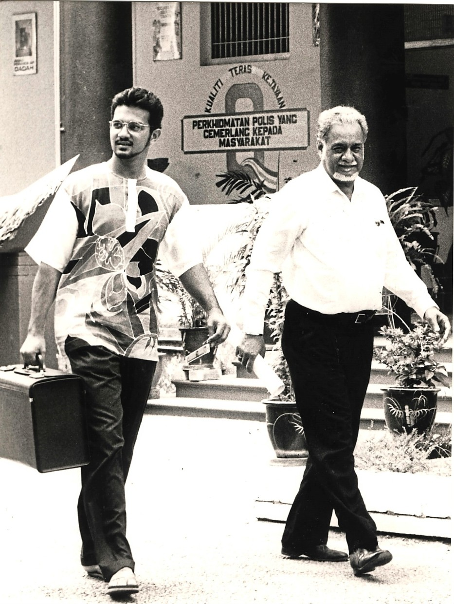 Like father, like son: Karpal (right) leaving the police headquarters in Penang after lodging a report in connection with a case he was working on in 1992 as Gobind is seen carrying his father's bag. — The Star