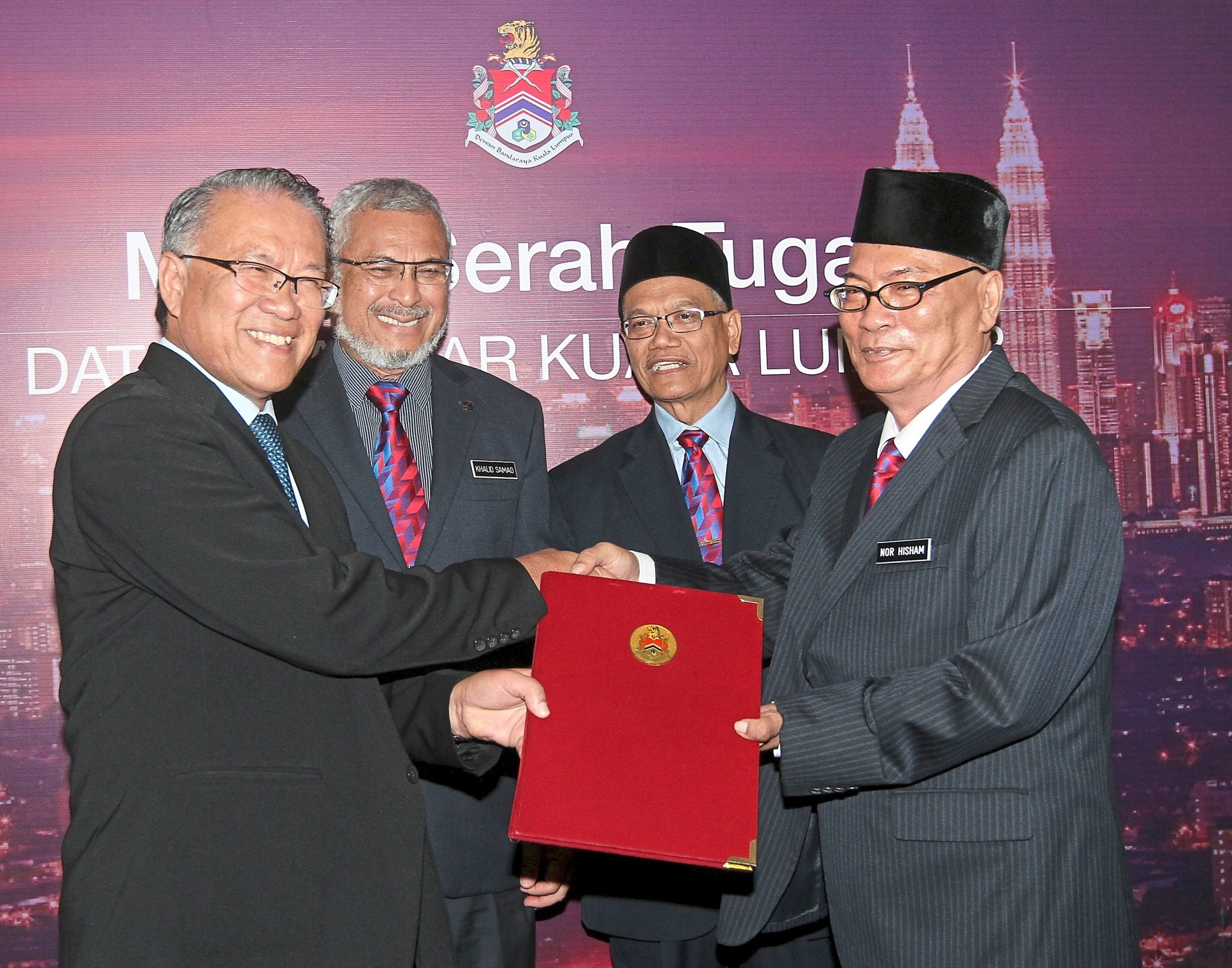 Outgoing Kuala Lumpur mayor Mohd Amin (left) handing over his duties to Nor Hisham last year. Looking on are Khalid (second from left) and Deputy FT Minister Datuk Dr Shahruddin Md Salleh. —filepic