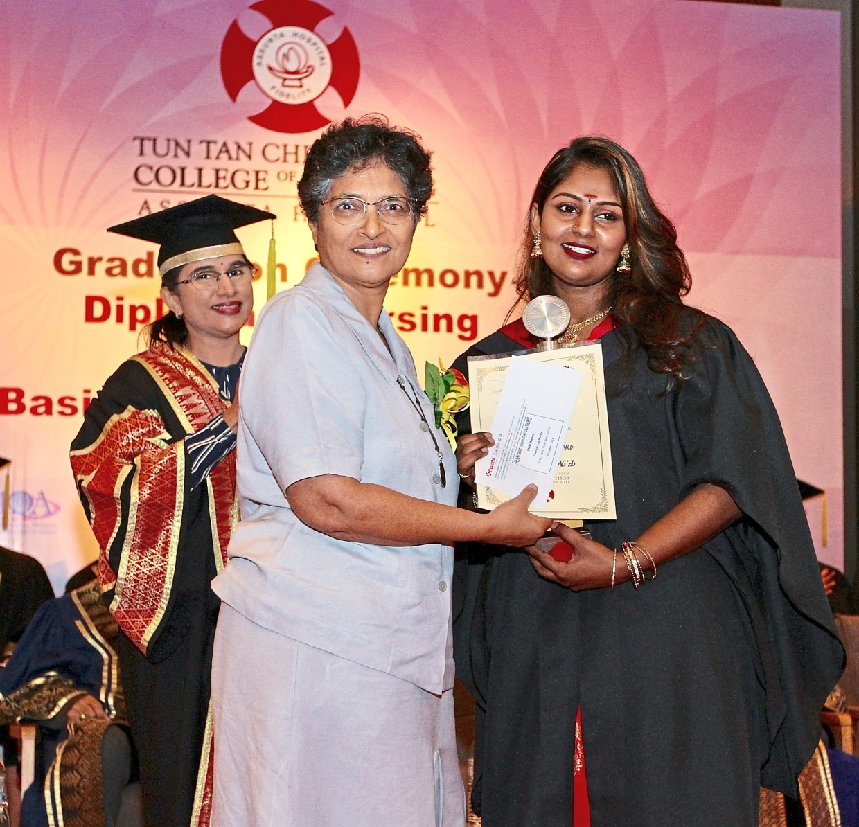 (From left) Theresa witnessing Sister Susan (in grey) present the FMM special award to Dharsini at the graduation ceremony in Petaling Jaya.