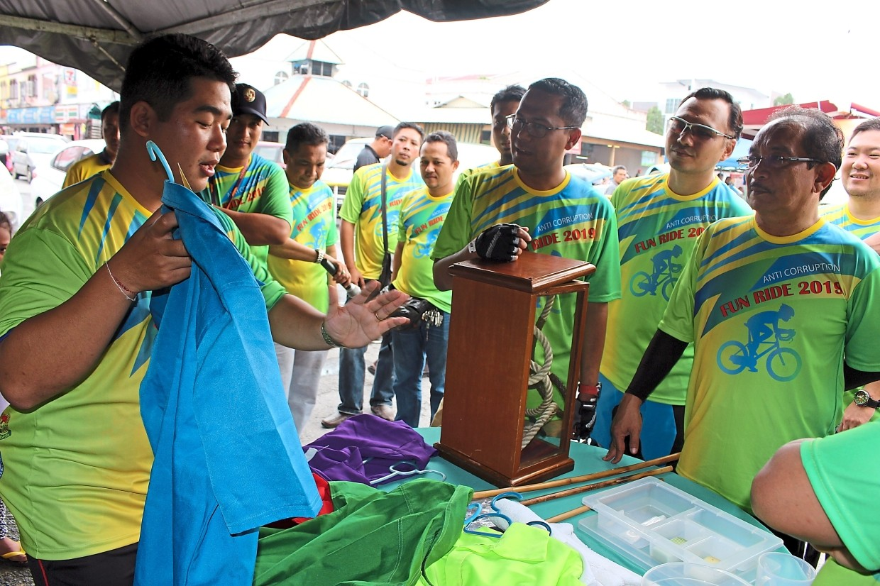 Alor Setar Prison officer Larry John (left) briefing (from right) Shaharom Nizam, Zuhri Hamid and Mohd Asmirul on the inmates' uniform during their visit to the Kedah Prison Department exhibition booth.