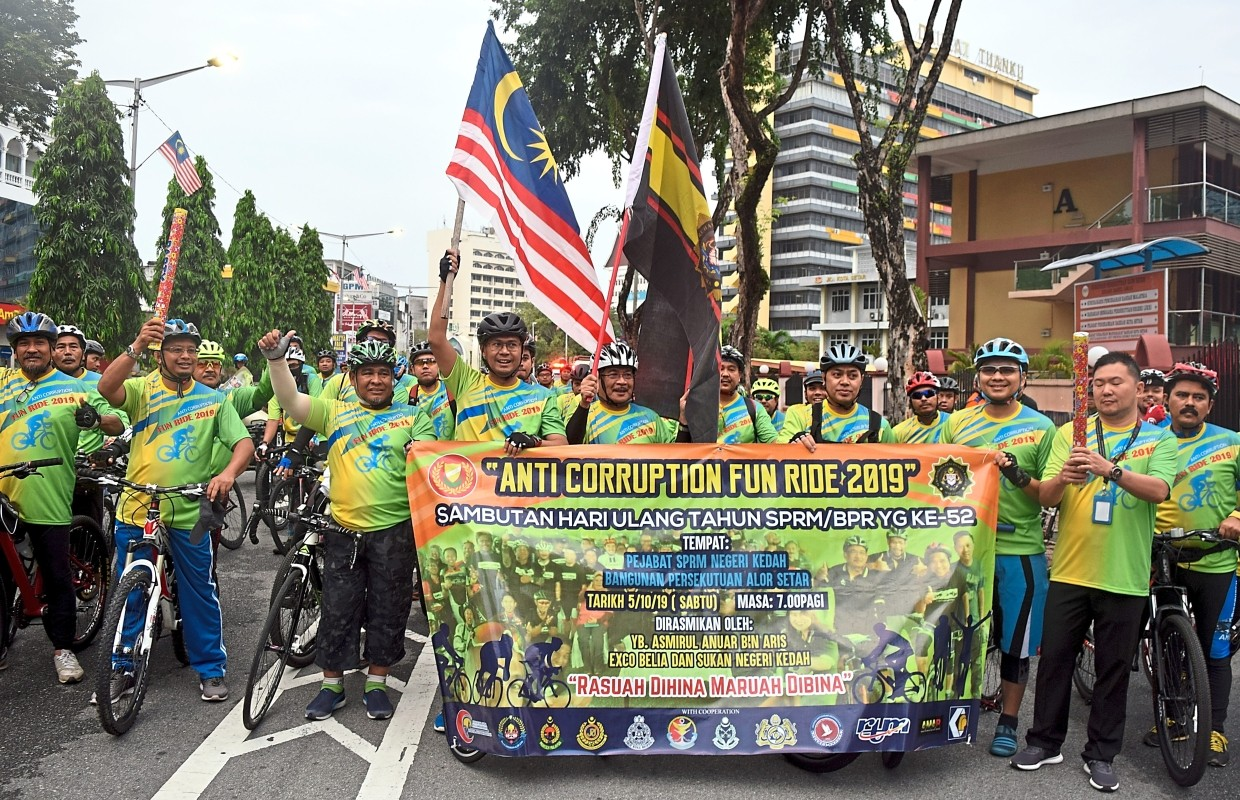 Shaharom Nizam (centre, raising the MACC flag) and Mohd Asmirul  (hoisting the Jalur Gemilang) posing with the 100 cyclists from 12        government agencies before the flag-off of the Anti-Corruption Fun Ride 2019 outside the Kedah MACC headquarters in Jalan Sultan Badlishah, Alor Setar, Kedah.