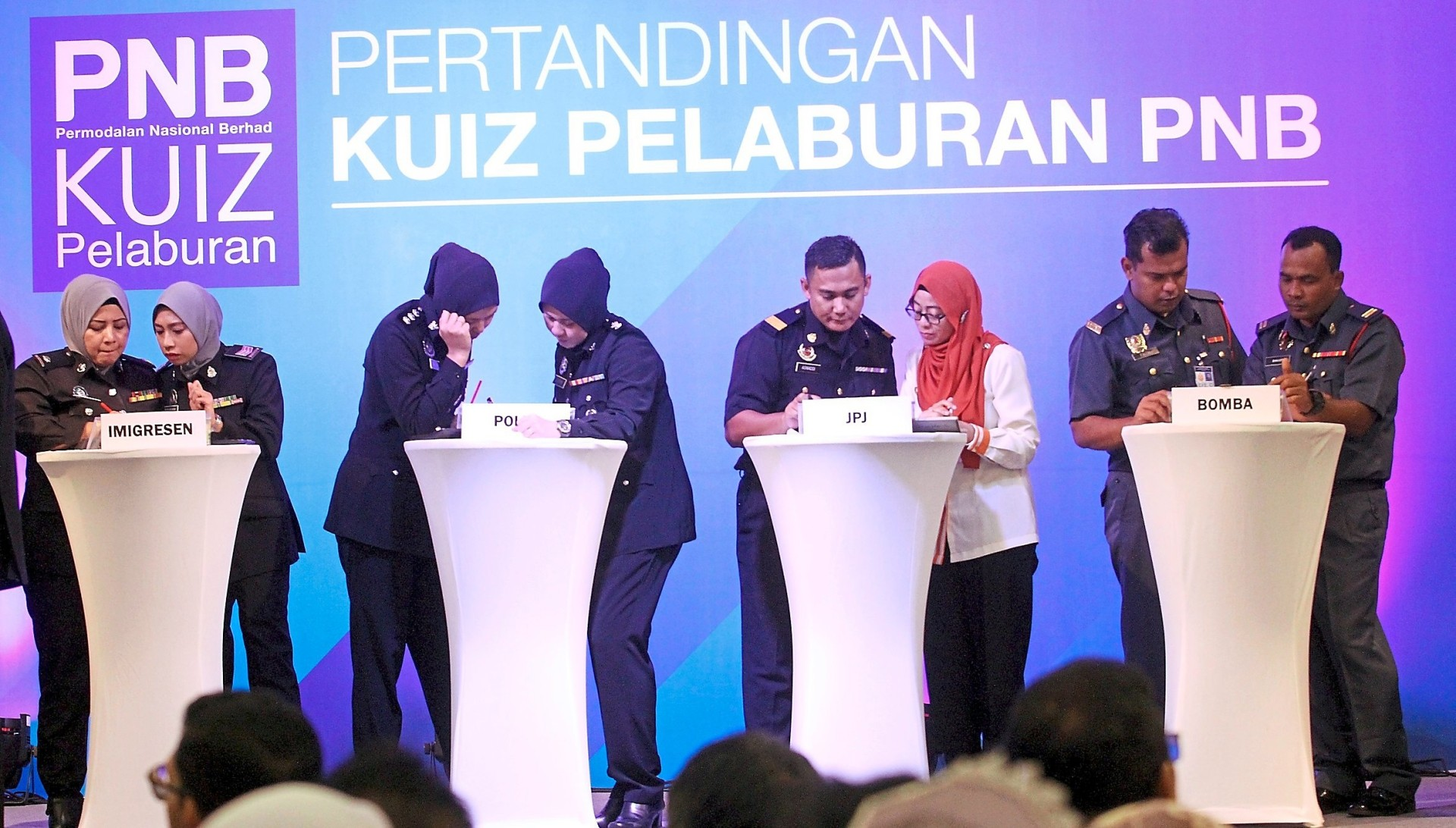 Finalists in the uniformed bodies category answering questions during the PNB investment quiz 2019 in Puchong.