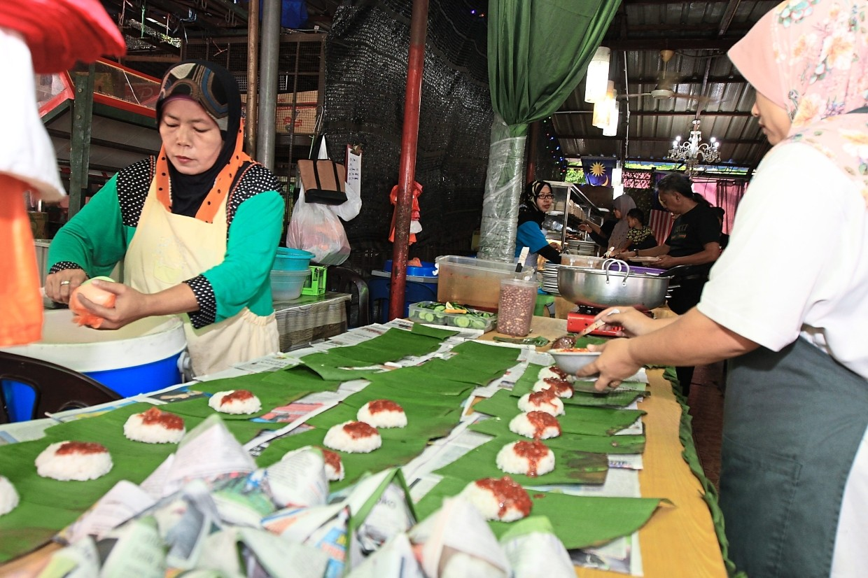The 50sen nasi lemak is laid out in rows as Warong Kaklong staff add the necessary ingredients before wrapping them up.
