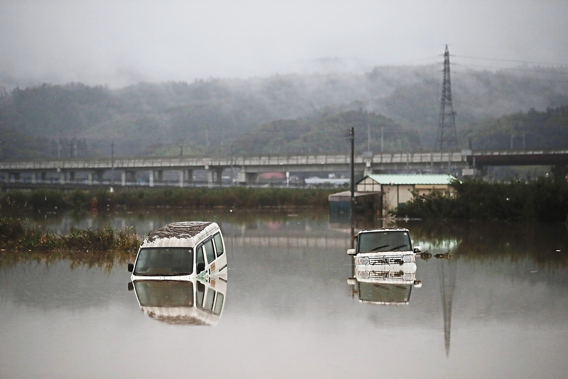 Two vehicles are submerged in floodwaters in the Nagano area due to Typhoon Hagibis onslaught. — AFP/AP