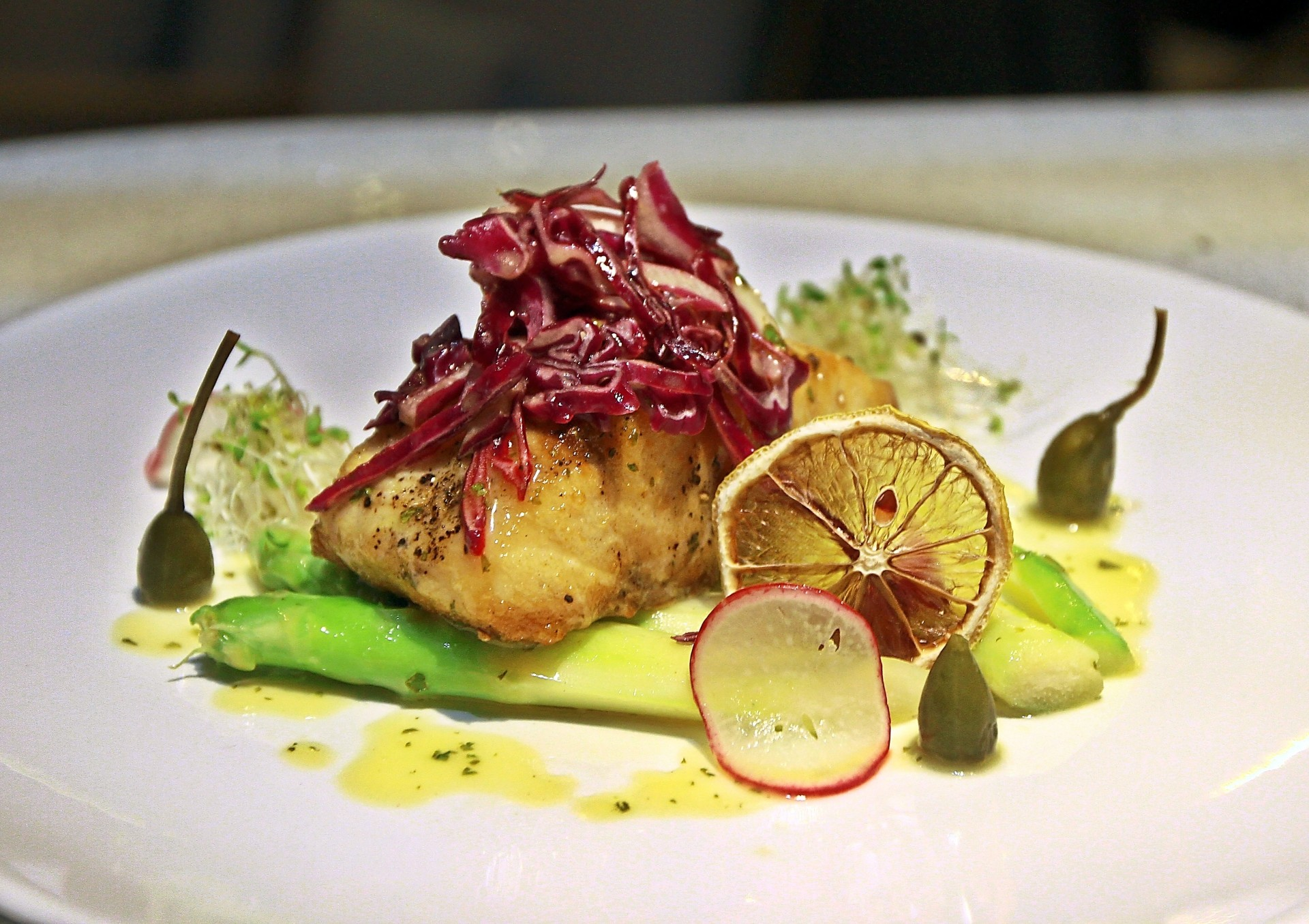 Roasted Barramundi fillet served with green asparagus, red cabbage slaw, capers and lemon sauce.