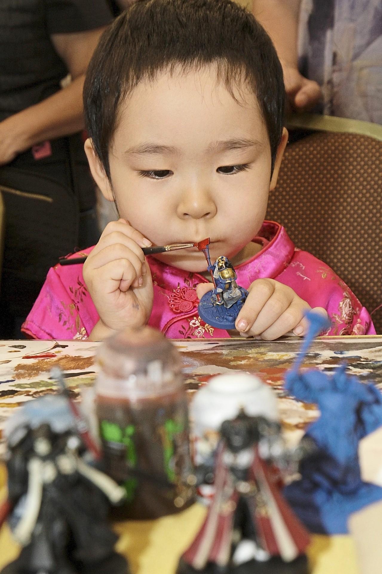 Ting Jiao, four, painting a miniature sculpture.