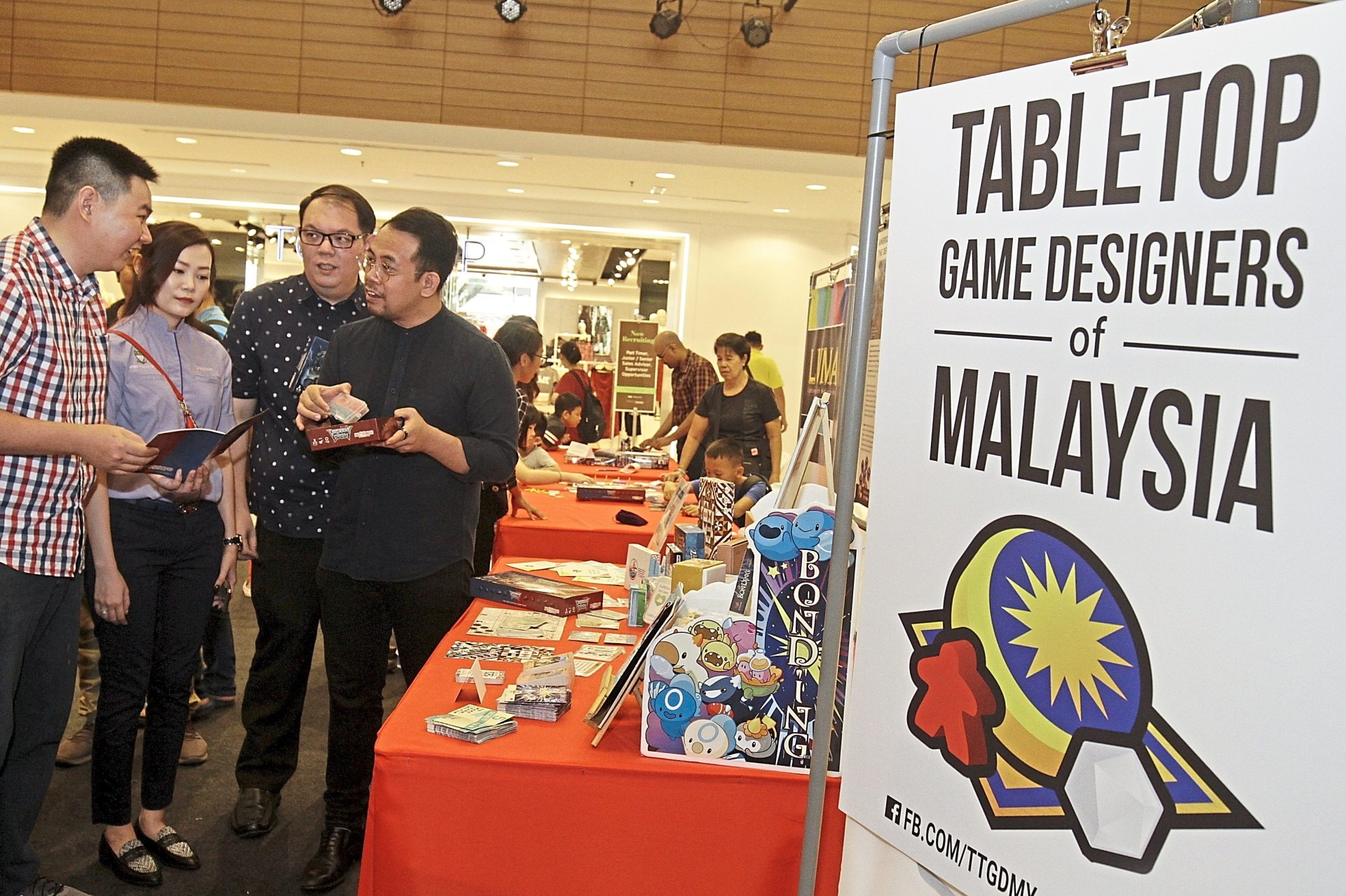 (From right) Sim and Lee checking out the games at the 'Tabletop: The Awakening' event.