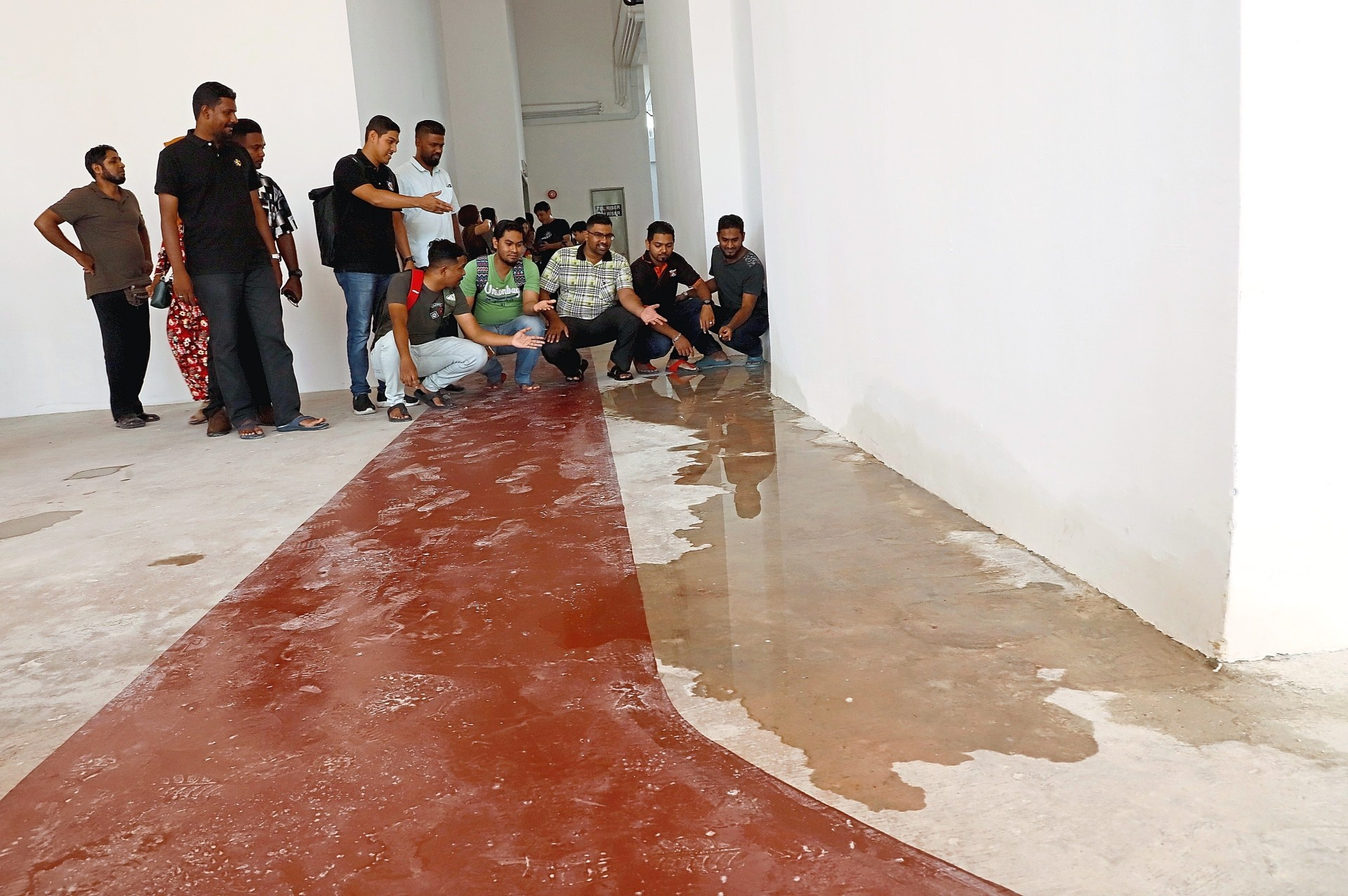 Residents showing water leakage along the community facility floor.