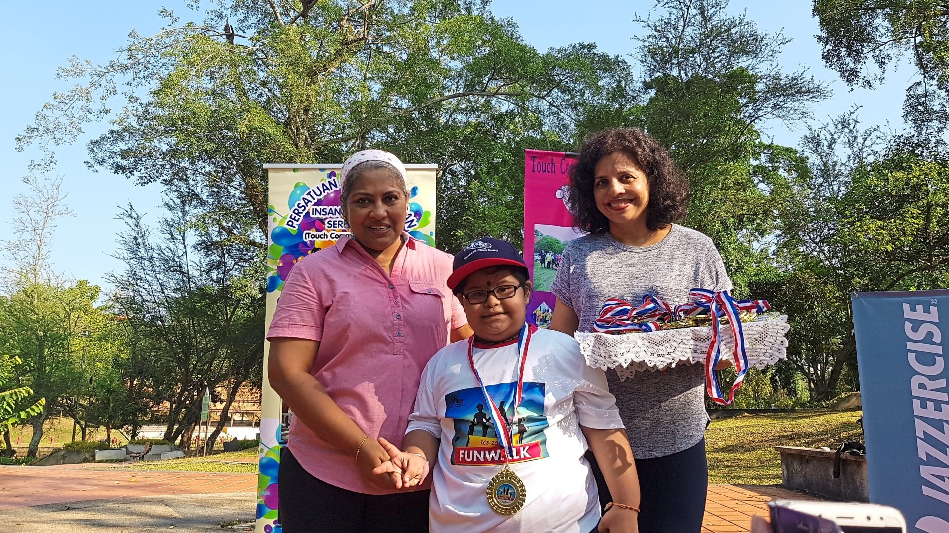 Janeve (centre) smiles after receiving her medal from Sunitha (left) and Dr Pushpa.